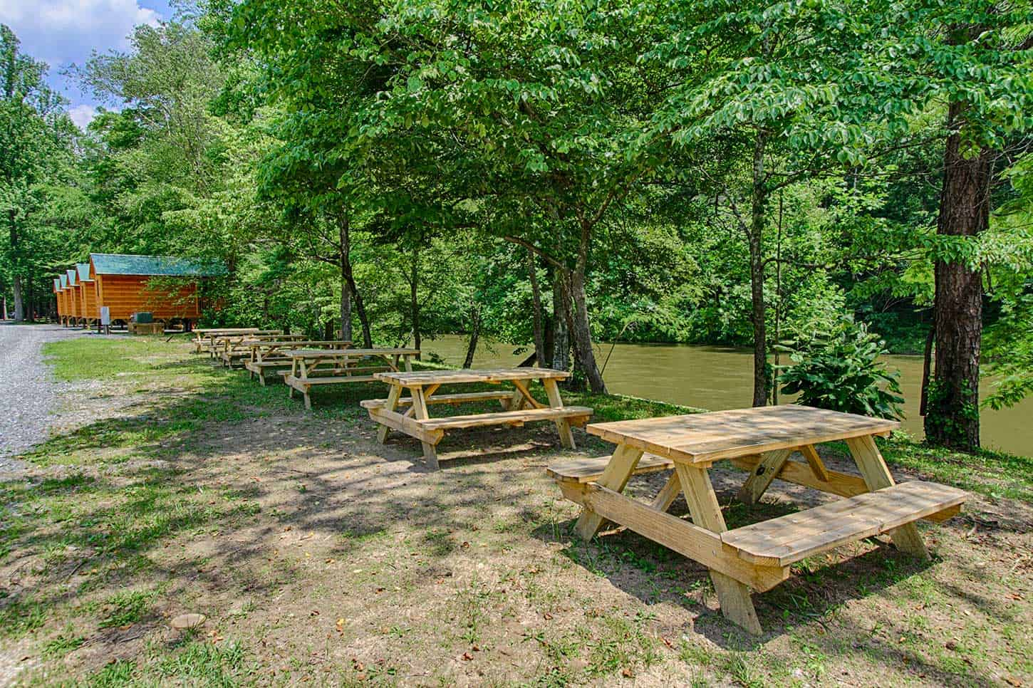 Cabins and picnic tables along the Pigeon River at a campground in the Smoky Mountains