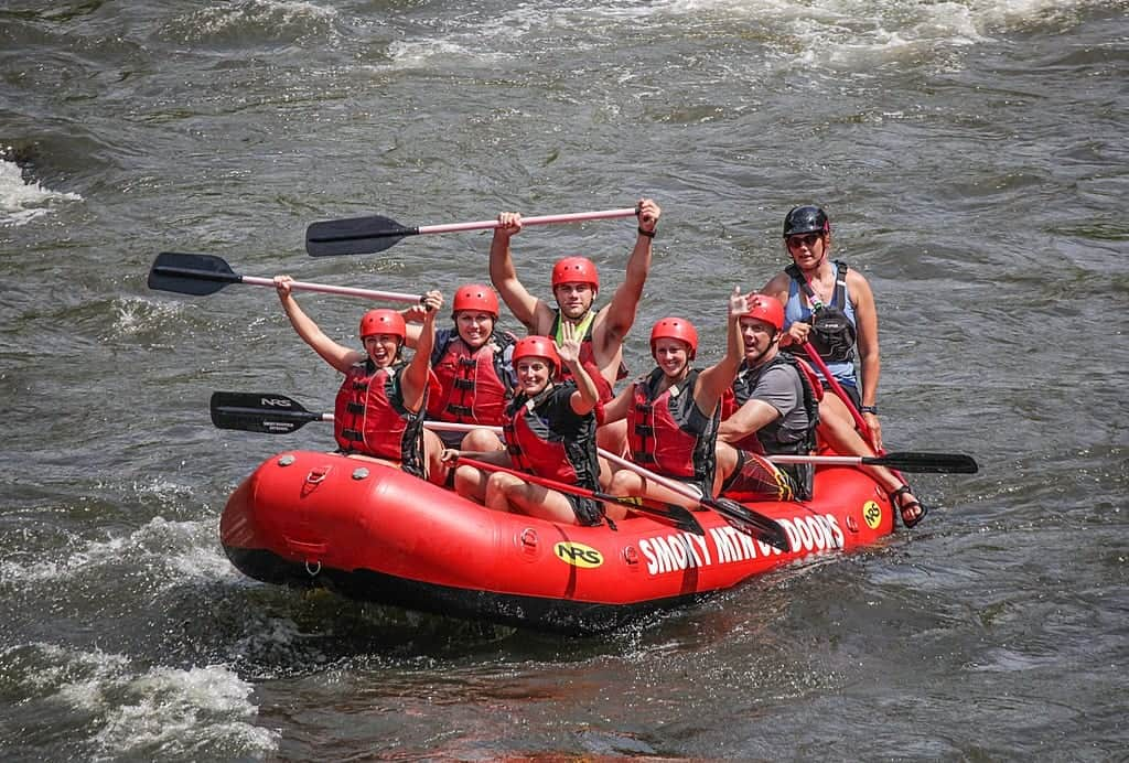 A happy group of people white water rafting near Gatlinburg at Smoky Mountain Outdoors.