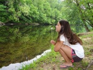 Closeup of a girl with a dandelion on the Little Pigeon River.