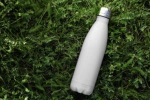 stainless steel water bottle laying on the grass